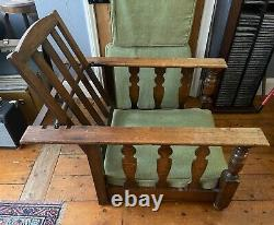 A pair of vintage arts and crafts style adjustable oak lounge chairs